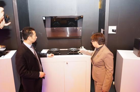 中国家用电器协会副理事长王雷(右)与红顶奖组委会负责人吕盛华为华帝精控灶贴标