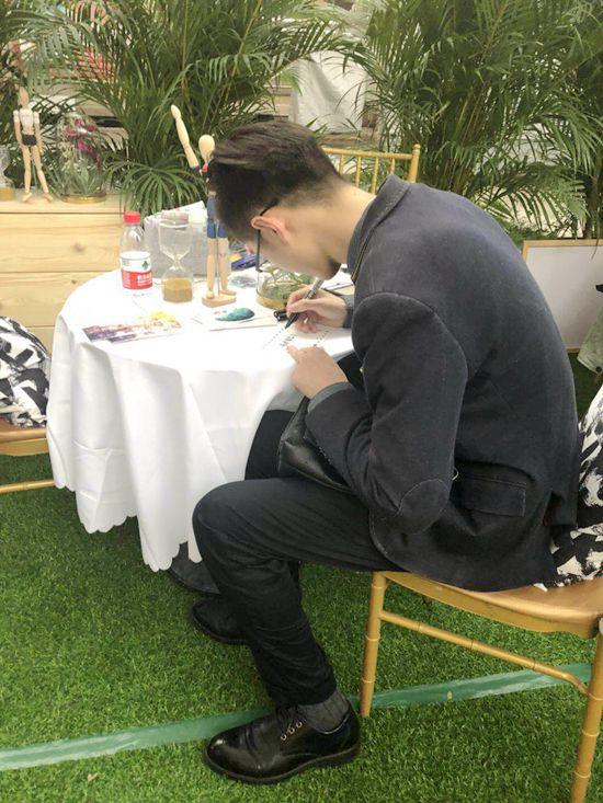 参与活动的年轻男士在明信片上写下对未来生活的期许