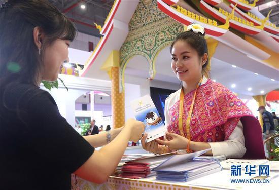 11月7日,在首届中国国际进口博览会上,老挝展区工作人员(右)在向参观者先容情况。新华社记者 陈飞 摄