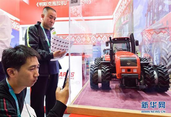 11月7日,参观者在拍摄、观看白俄罗斯明斯克拖拉机厂的拖拉机模型。 新华社记者 李贺 摄