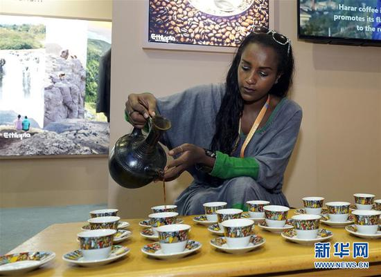 11月6日,在首届中国国际进口博览会上,埃塞俄比亚参展人员为参观者倒咖啡。新华社记者 沈伯韩 摄