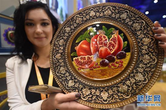 11月8日,乌兹别克斯坦参展人员展示手工制作的核桃木工艺品。 新华社记者 韩瑜庆 摄