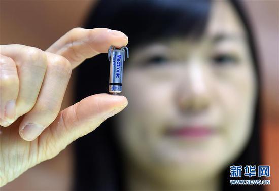 11月8日,在进博会医疗器械及医药保健展区美敦力企业展台,工作人员在展示全球最小的心脏起搏器。新华社记者 韩瑜庆 摄